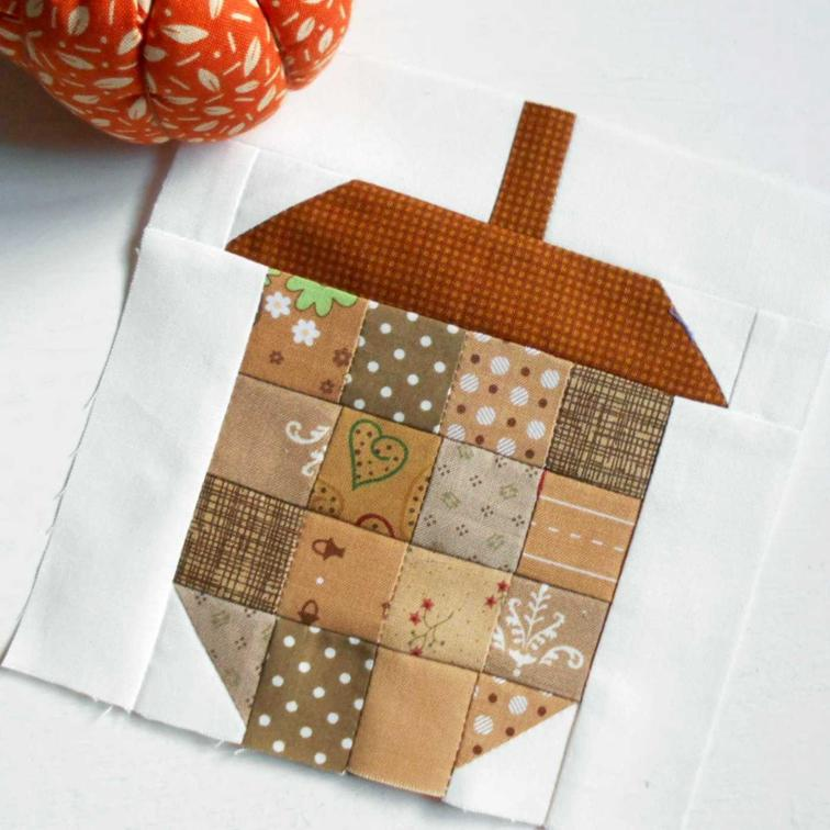 15 Fabulous Patterns for Fall - Scrappy Patchwork Acorn - Let me share some really great patterns and inspiration with you so you can start creating! Check out these 15 fabulous patterns for fall! #simple #TableRunners #AutumnLeaves #JellyRolls #WallHangings #FallQuiltBlocks #Quilting #ColorCombos #Fabric #PaperPiecing #Fun #Easy #Quick #pattern